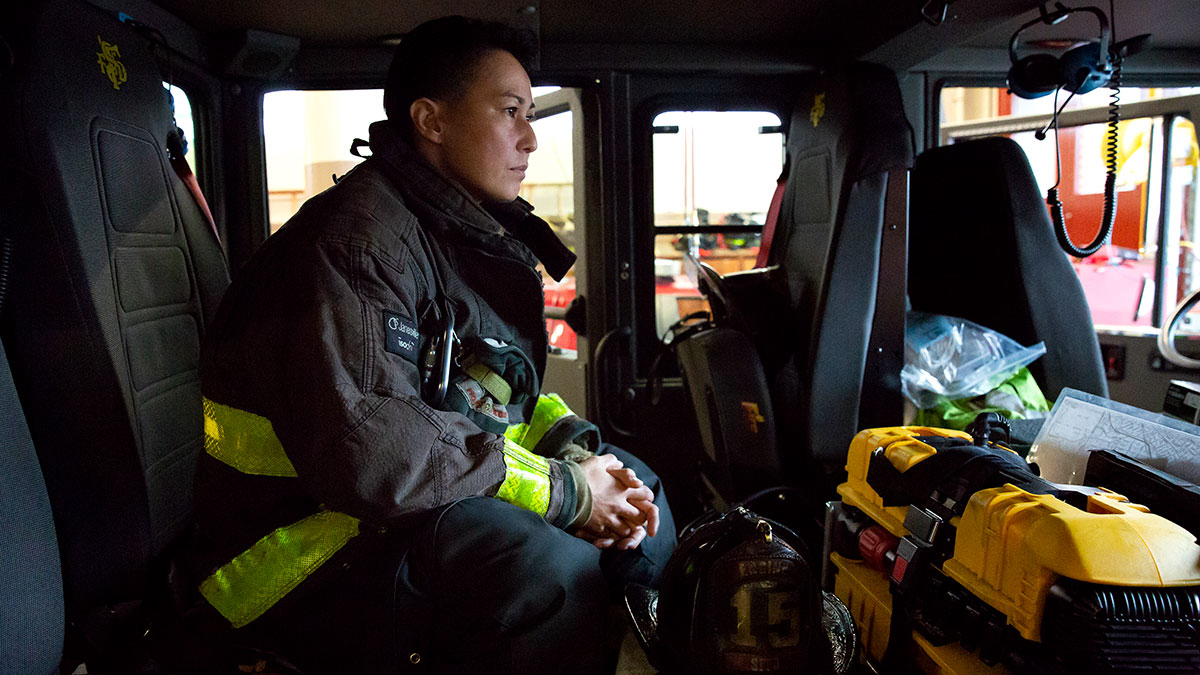 A woman firefighter sits in the cab of a firetruck in her jacket and gear.