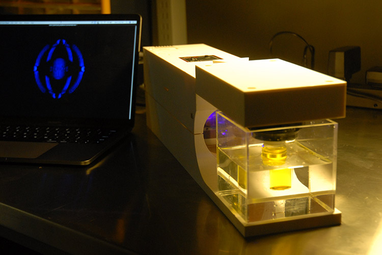 A photo of the 3D printer next to a computer screen