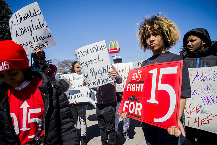 a group holds signs in favor of the minimum wage