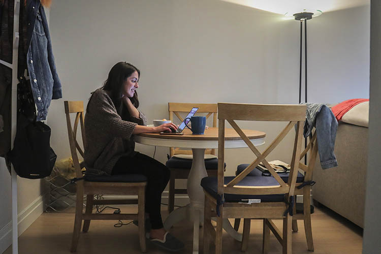 a woman works at a laptop at her apartment dining room table