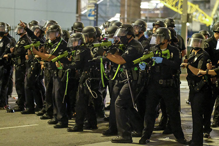 A line of police officers in riot gear point weapons containing rubber bullets at protesters in Los Angeles following the death of George Floyd, a black man who was killed in police custody on May 25.
