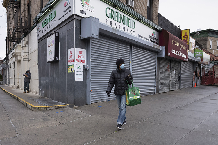 A lone woman, wearing a medical mask, walks past shuttered storefronts in New York City, the epicenter of the COVID-10 pandemic in the United States.