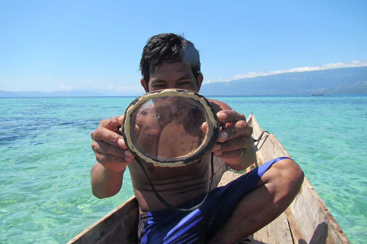 A Bajau diver, sitting in a boat on the water, carrying a mask that he made