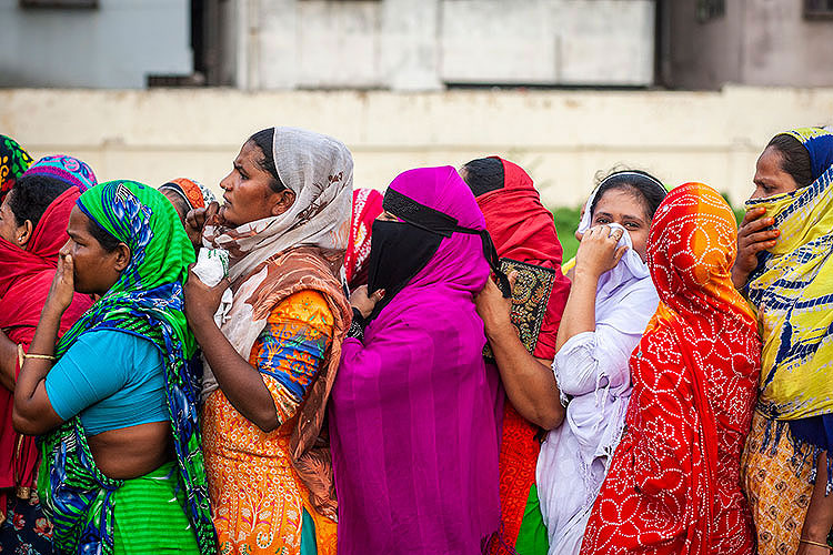 women in Bangladesh in a crowded line await COVID-relief aid