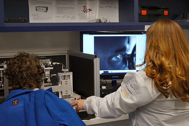 A woman wearing a white lab coat facing a computer scanning a patient's eye.
