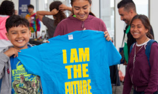 "students hold blue shirt that reads ""I AM THE FUTURE"""