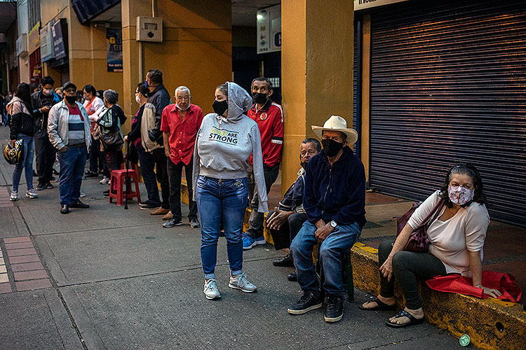 people of different ages wait in line for pandemic-relief aid in Medillin, Colombia