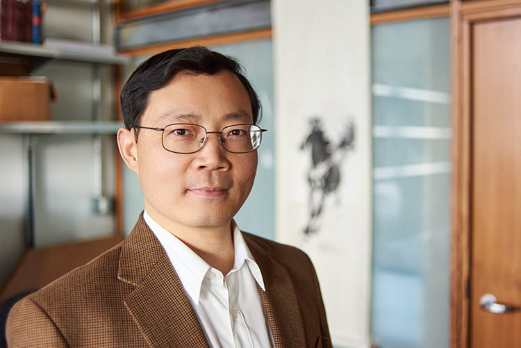 Junqiao Wu looks at the camera while standing in his lab