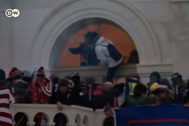 Rioters entering the U.S. Capitol through a broken window