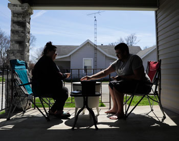 A couple in Greensburg, Indiana plays a card game on the front porch