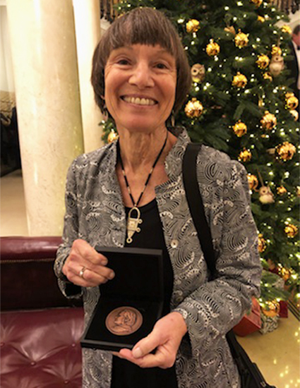 Margaret Conkey holding the Thomas J. Huxley Memorial Medal
