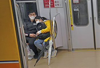 A masked couple in Tokyo rides the subway