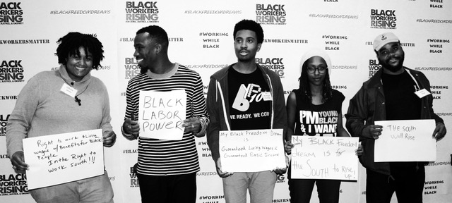 Group of people holding signs in front of Black Workers Rising background