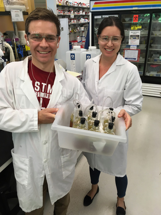 Charles Denby and Rachel Li in lab coats holding a box of vials