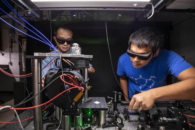 Co-lead authors Satcher Hsieh (left) and Chong Zu tune the laser of their imaging system. When excited by laser light, NV centers emit photons whose brightness informs researchers about the local environment that they are sensing.