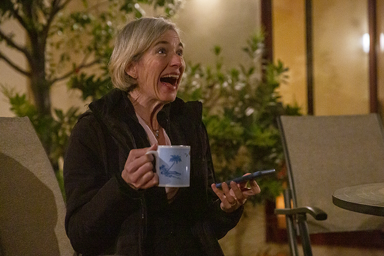 Jennifer Doudna laughs with a cup of coffee in her hand and a phone in the other hand