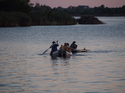 people in canoe on water at dusk