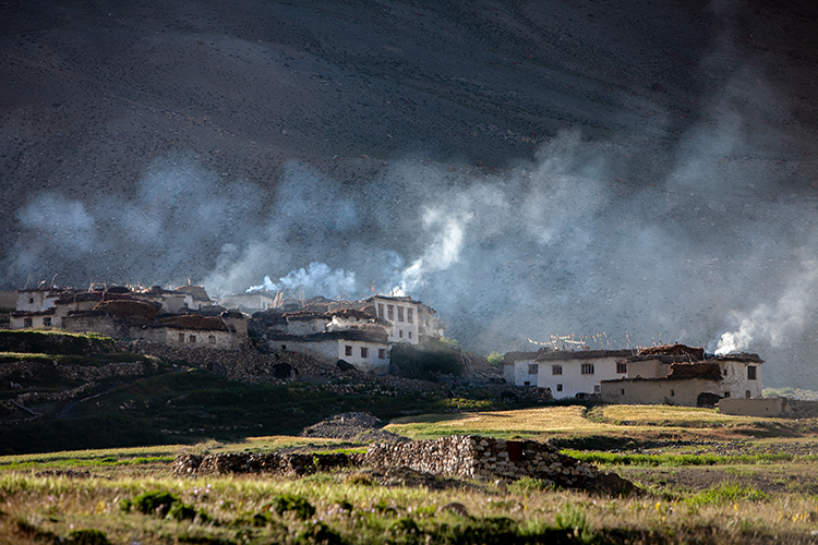 Photo shows houses on a hillside with smoke emerging from smokestakcs