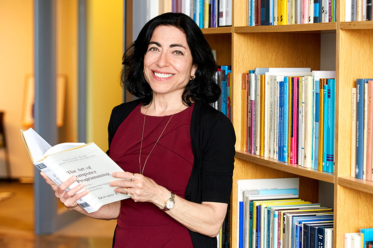 A photo of Jennifer Tour Chayes holding a book on computer programming in front of a bookshelf