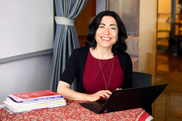 A photo of Jennifer Tour Chayes at a table with a laptop open in front of her