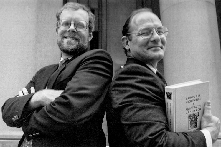 Portrait of John Hennessy and David Patterson, Patterson is holding a Computer Architecture and Quantitative Approach