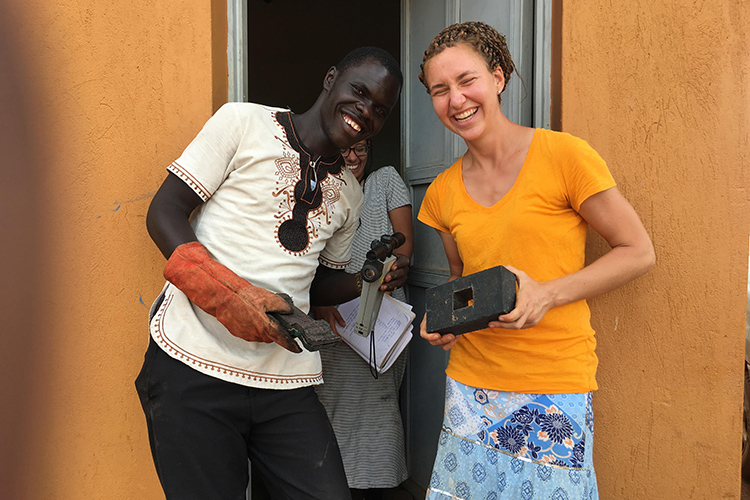 In Gulu, Uganda, Juliana Cabrera, a UC Berkeley undergraduate majoring in mechanical engineering, enjoys a laugh with Gulu University biosystems engineering student Felix Adupe after finishing an experiment at Takataka Plastics.