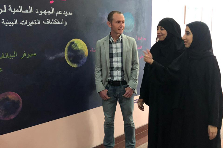 Rob Lillis talking with two UAE students wearing black abayas