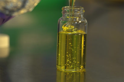 A thick yellow liquid is being poured into a small vial.