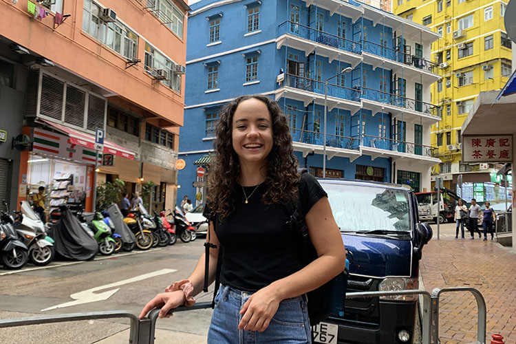 Maria Isabel Di Franco Quiñonez smiles while standing in front of colorful high-rise buildings.
