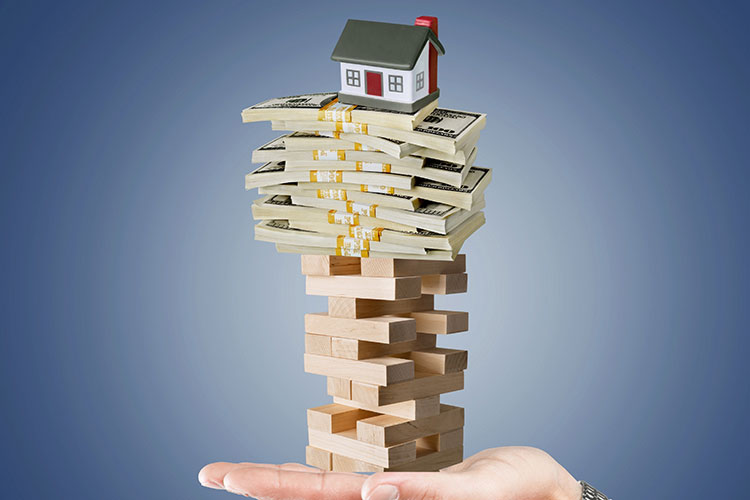 Graphic of a hand holding a house on top of a pile of a cash, both on top of a jenga set