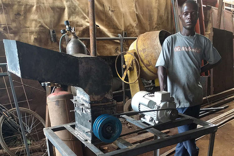 Mugaiga Ronald, a Gulu University student who worked as an intern at Takataka Plastics, poses with the prototype shredding machine he worked on.