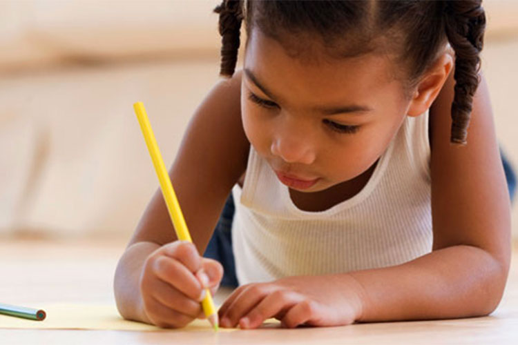 Image of pre-K child on floor writing