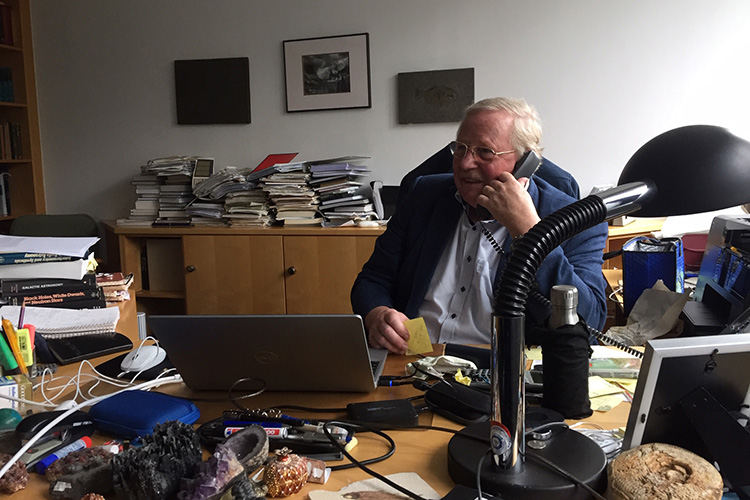 Reinhard Genzel on the phone in his office