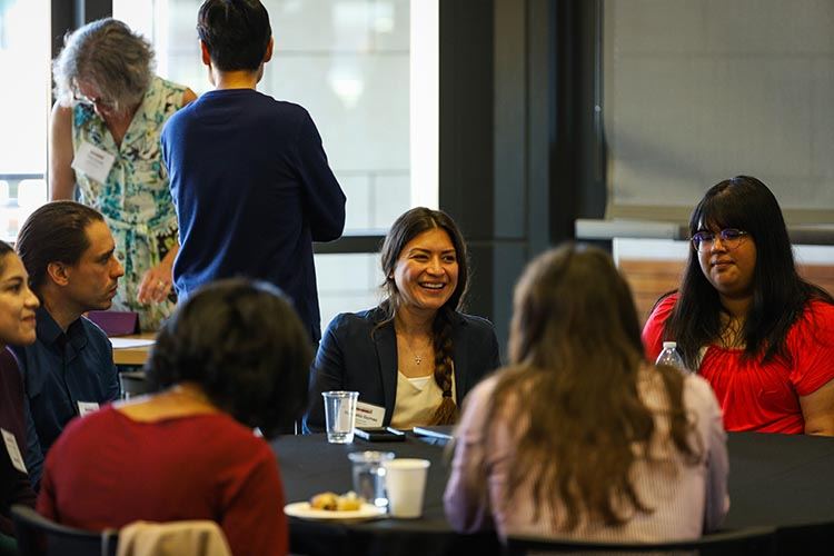 Marcella Gomez is an alumna of the California Alliance and today is an assistant professor at UC Santa Cruz. Here she is pictured at a table at Stanford University, talking with other attendees of the California Alliance's 2019 retreat.