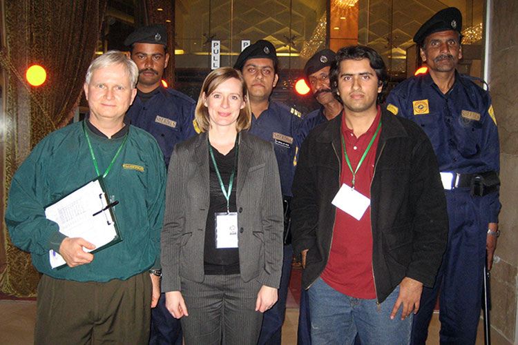 Susan Hyde (front row, center) stands with a colleague, an interpreter and a security detail during travel to Islamabad, Pakistan, in 2008 as part of a Democracy International election observation mission.