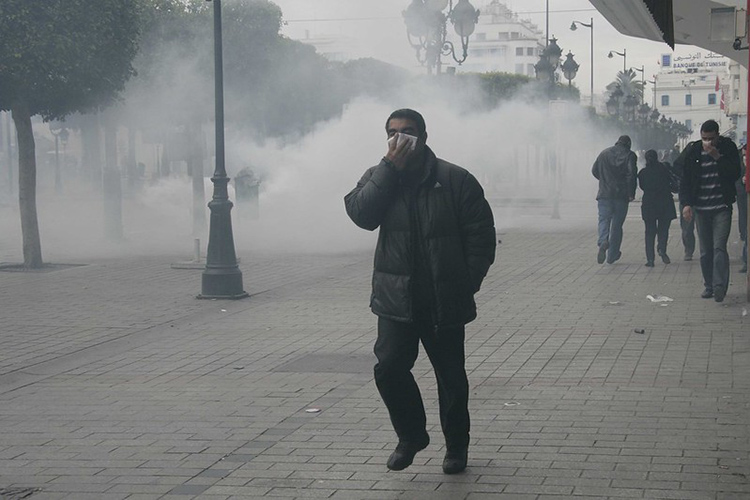 A man flees tear gas deployed at a 2011 demonstration in Tunis.