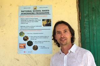 Miguel stands with a deworming poster in from of a stucco wall