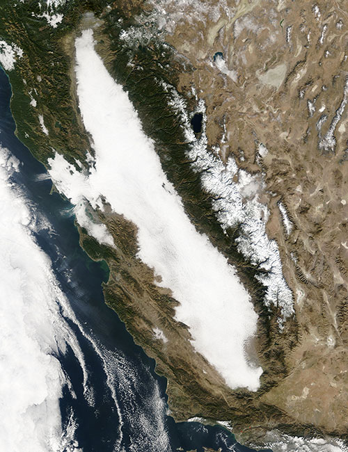 A satellite image of the Central Valley of California, showing thick white clouds in the valley