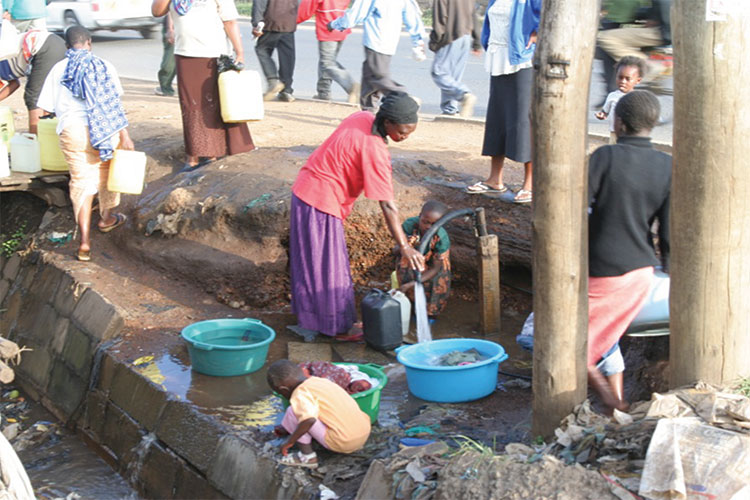 A photo of a woman in Nairobi filling a bucket with water