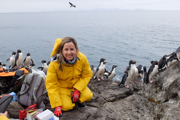 Juliana Vianna in a yellow parka among a group of rockhopper