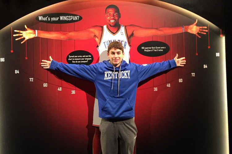 A boy stretches his arms out while standing in front of a life-size photo of Kevin Durant's wingspan