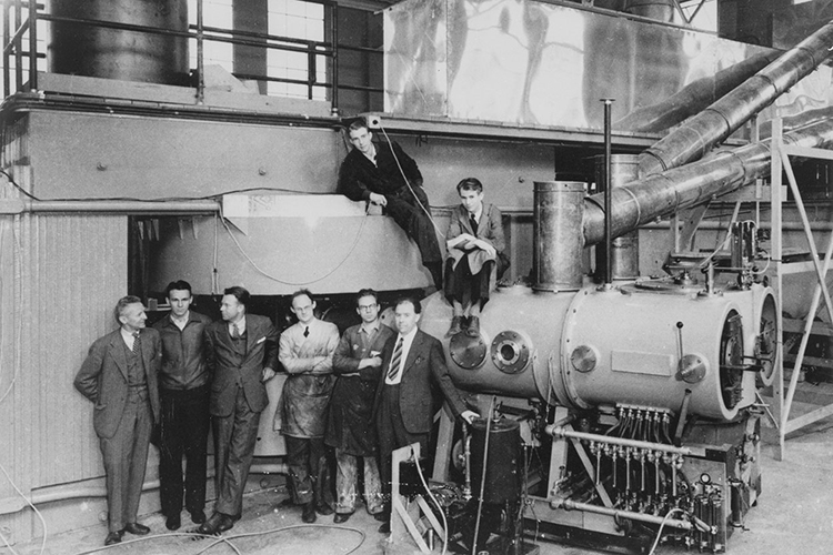 8 people standing in a line next to the 60-inch cyclotron, Ernest Lawrence being the third person from the left