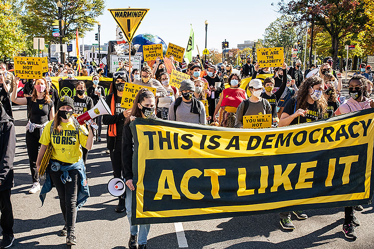 "Protesters carry a sign saying: ""This is a democracy 