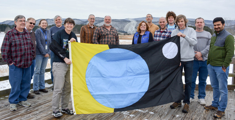 "Astronomer Vishal Gajjar (right) and engineer Dave MacMahon (holding flag) of UC Berkeley present the traditional SETI ""Flag of Earth"" to the crew of the Green Bank Telescope, including director Karen O'Neil (holding flag)"