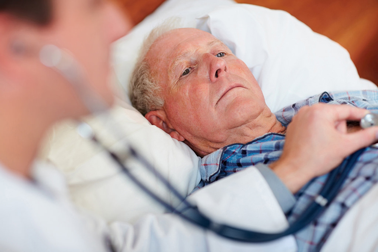 Man lying in bed, doctor using a stethoscope on him
