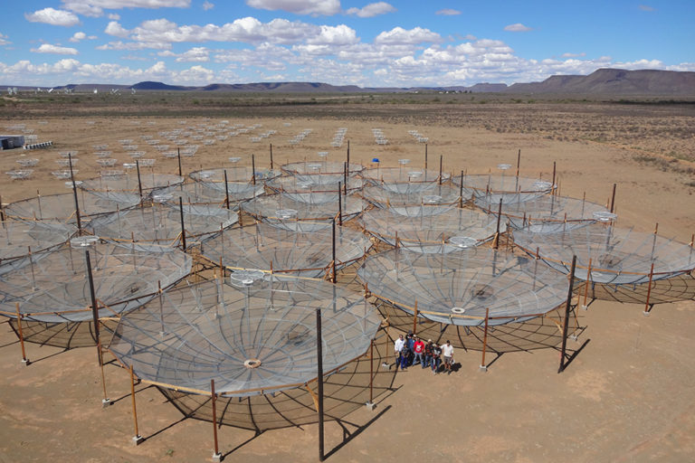 The HERA array in South Africa consisted of 19 dishes on March 7, 2016, but continues to grow, replacing an earlier experiment called PAPER (small dishes in the background). (Images courtesy of the HERA team)