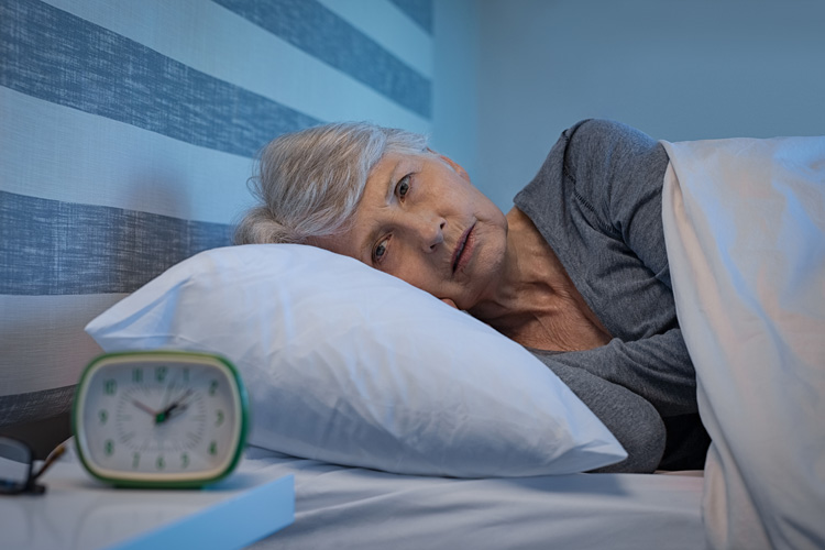 woman awake, staring at clock