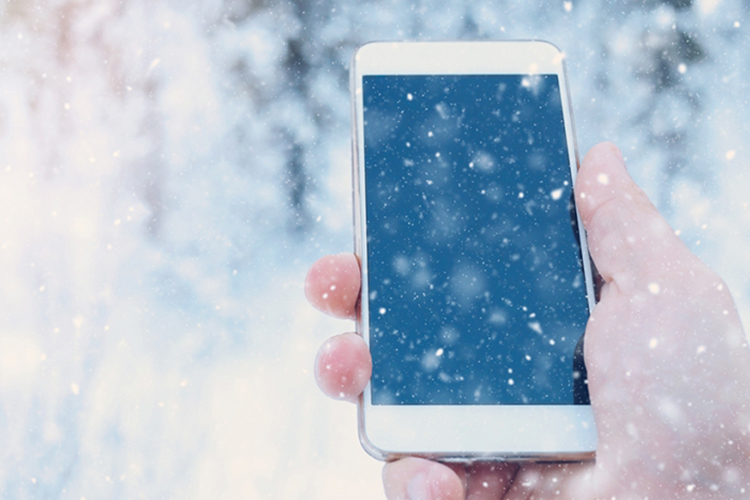 A hand holding an iPhone in snowy weather