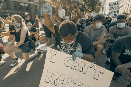 Protestor holding up his fist in solidarity in Charlotte, NC (Photo: Clay Banks via Unsplash)