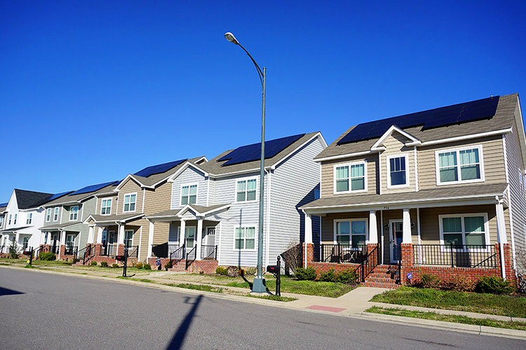 row of houses with solar panels on the roofs